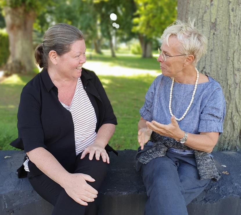 Anki Mattson och Karin Dellby sitter i en park och pratar med varandra.
