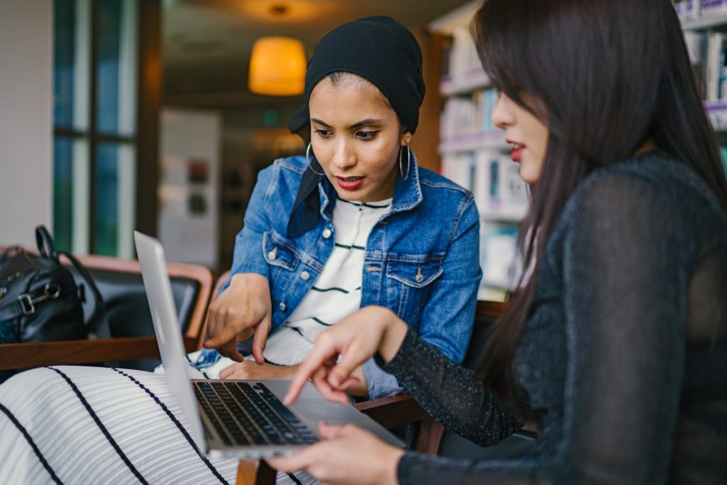 Två personer som arbetar och läser på en dator tillsammans.