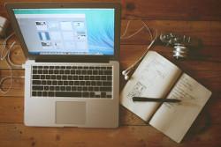 En dator och ett anteckningsblock som kan användas vid textredigering.